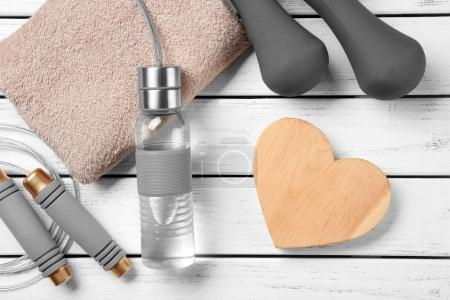 Gym stuff and heart on wooden background. Cardio training concept