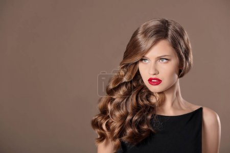 Photo for Beautiful young woman with long wavy hair on color background - Royalty Free Image