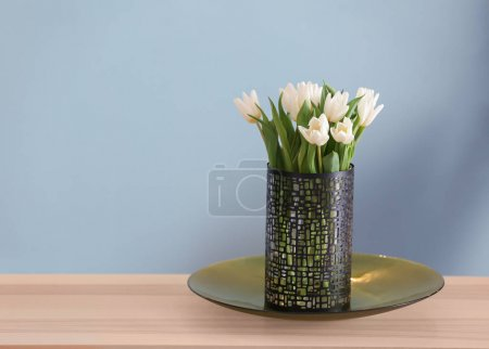 Vase with bouquet of tulips on wooden table in living room