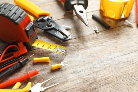 Different electrical tools on wooden background