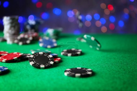Gambling chips on green table in casino