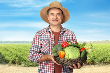 Agronomist holding dish with various vegetables in field