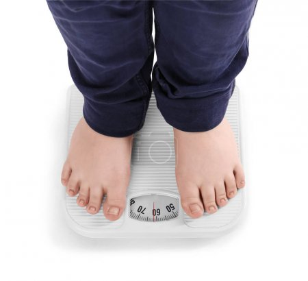 Overweight boy standing on floor scales against white background