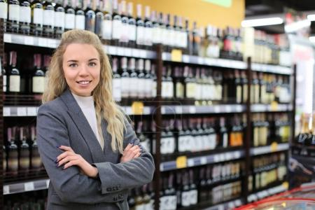 Portrait of young woman in liquor shop. Small business owner