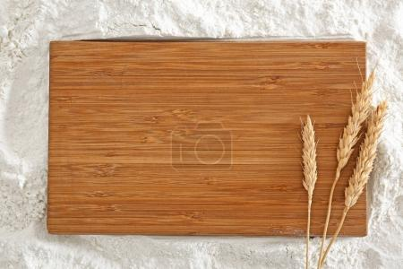 Wooden board with spikelets on flour