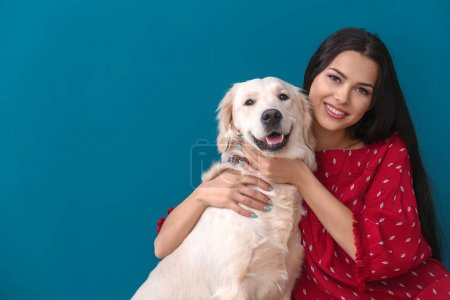 Young woman with dog on color background. Friendship between pet and owner