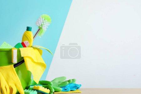 Photo pour Seau avec des fournitures de nettoyage et des outils sur la table près du mur de couleur - image libre de droit