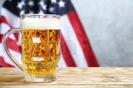 Photo pour Verre de bière sur la table, sur fond de drapeau américain - image libre de droit
