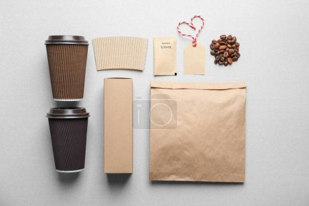 Composition with blank cups as mock ups for branding on grey background