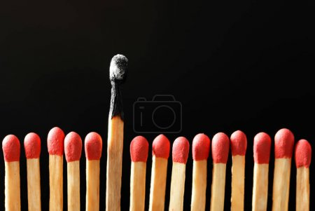 Burnt match among others on black background. Difference and uniqueness concept