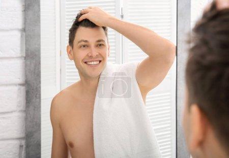 Handsome shaved man near mirror in bathroom
