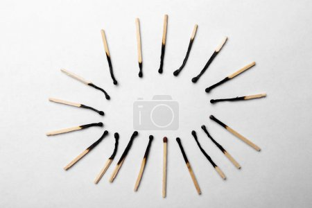 Burnt matchsticks and one different on white background