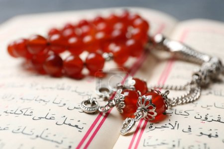 Opened holy book of Muslims and prayer beads