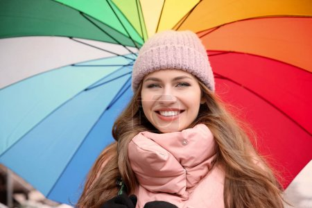Young woman with rainbow umbrella outdoors
