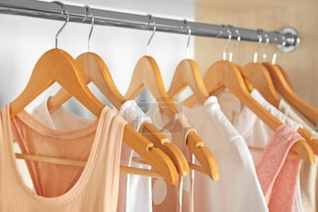 Photo for Hangers with different clothes in wardrobe closet - Royalty Free Image