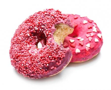 Delicious glazed doughnuts with sprinkles on white background