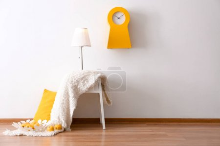 Photo for Elegant lamp and blanket on table in room interior near light wall - Royalty Free Image