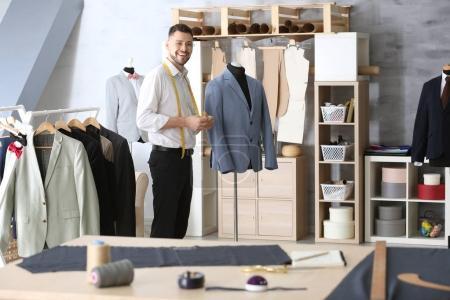 Photo pour Beau jeune tailleur en atelier - image libre de droit