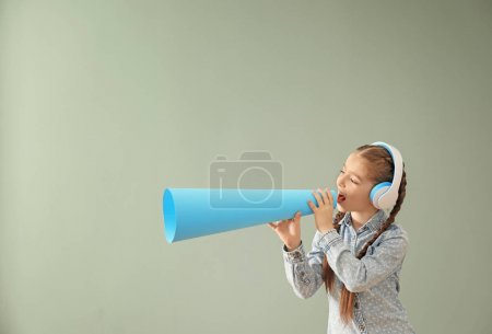 Little girl with headphones and paper megaphone on color background