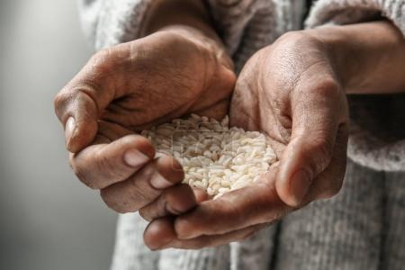 Poor woman holding rice in hands, closeup