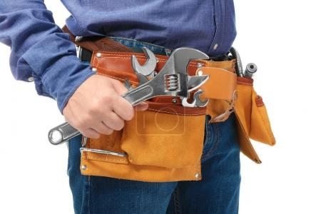 Plumber with tool belt and wrench on white background, closeup