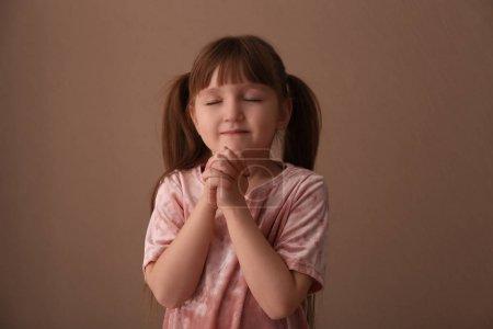 Photo pour Fille de Christian religieuse priant sur fond marron - image libre de droit