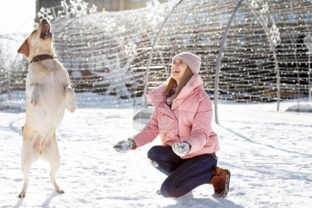 Woman playing with cute dog