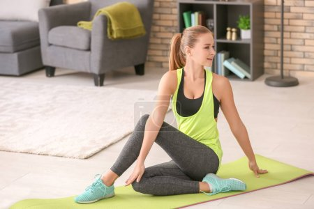 Photo for Beautiful young woman doing fitness exercise at home - Royalty Free Image
