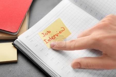"""Woman pointing at note with words """"Job interview"""" in notebook, closeup"""
