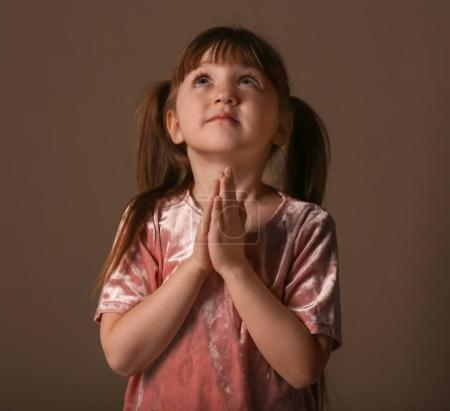 Religious Christian girl praying on dark background