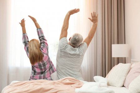 Mature couple stretching on bed. Romantic morning