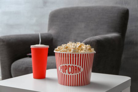 Tasty popcorn and drink on table, closeup. Home cinema