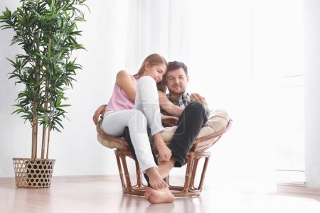 Cute young lovely couple sitting in armchair at home
