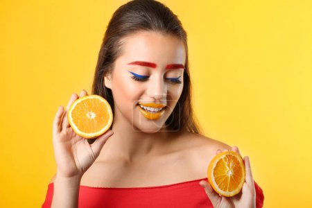 Young woman with dyed eyebrows and halves of orange on color background