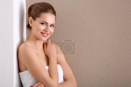Young woman applying cream onto her skin against color background