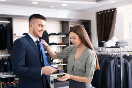 assistant helping man to choose suit
