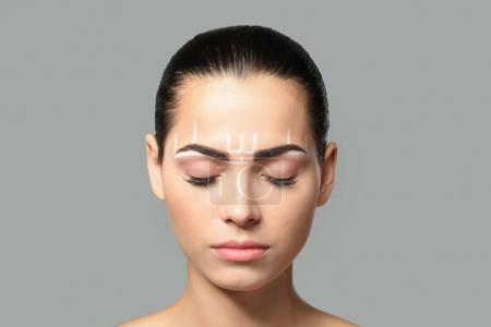 Photo pour Jeune femme avant la procédure des sourcils maquillage permanent sur fond gris - image libre de droit