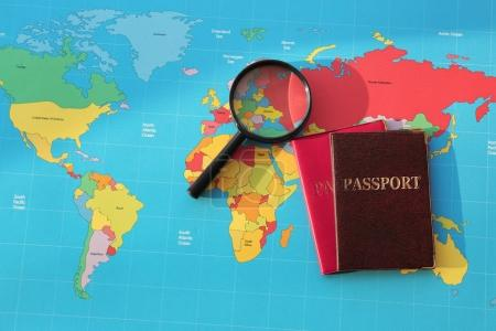 Magnifying glass, passports on world map. Immigrat...