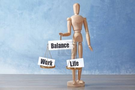 Wooden figure holding scales with words WORK, LIFE and BALANCE on table