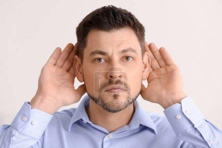 Photo pour Homme d'âge mûr avec problème d'audition sur fond clair - image libre de droit