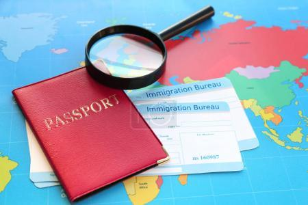 Magnifying glass and passport with arrival cards of immigration bureau on world map