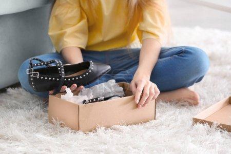 Photo pour Jeune femme déballage des colis à la maison - image libre de droit