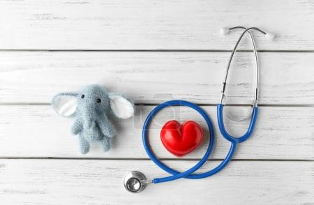 Cute knitted elephant, small heart and stethoscope...