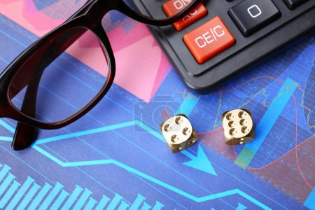 Dices, glasses and calculator on stock data graph, finance trading concept