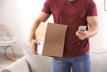 Photo pour Jeune homme faisant appel au sujet des colis livrés à domicile - image libre de droit