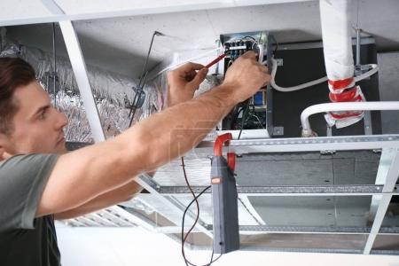Photo pour Technicien mâle mesure de tension lors de la réparation de climatiseur industriel à l'intérieur - image libre de droit