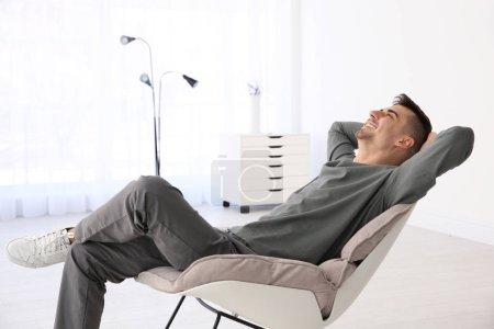 Photo pour Jeune homme reposant dans un fauteuil dans une pièce lumineuse - image libre de droit