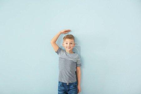 little boy measuring height near blue wall
