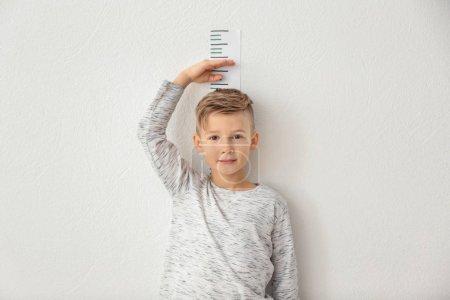 Foto de Niño midiendo altura cerca de la pared de luz - Imagen libre de derechos