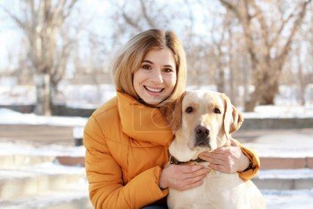 Photo pour Femme étreignant chien mignon à l'extérieur le jour de l'hiver. Amitié entre animal de compagnie et propriétaire - image libre de droit